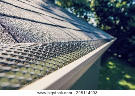 Plastic guard over gutter trough on a roof