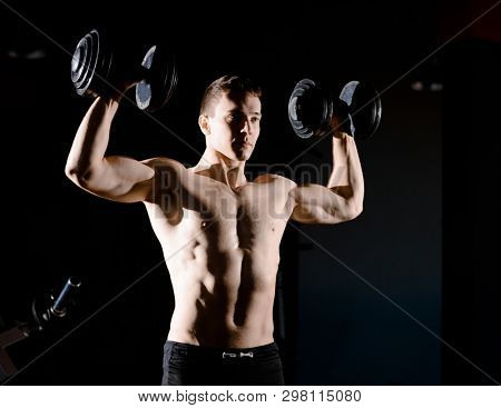 Portrait of Young Sportsman Lifting Heavy Dumbbells in the Dark Gym. Fitness and Healthy Lifestyle Concept. Dramatic Lighting