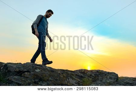 Young Happy Man Traveler Hiking with Backpack on the Beautiful Rocky Trail at Warm Summer Sunset. Travel and Adventure Concept.