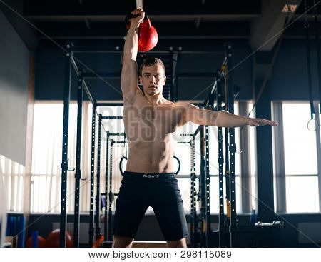 Young Sportsman Lifting Heavy Red Weight in the Modern Functional Gym. Fitness and Healthy Lifestyle Concept.