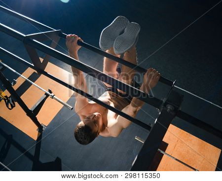 Young Sportsman Exercises on the Horizontal Bar in the Modern Functional Gym. Fitness and Healthy Lifestyle Concept. View from the Top