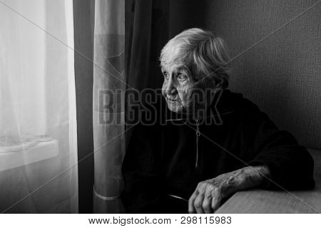 An elderly woman in his house looks out the window longingly. Old lady retired. Black and white photo.