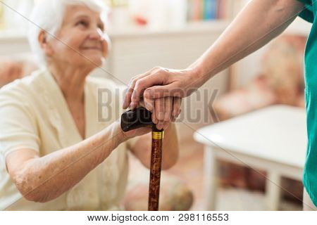 Close-up of woman holding senior's hands leaning on walking cane