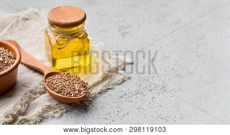 Linseed Oil, Bowl And Spoon Of Linseeds On Napkin Over Concrete Background, Copy Space. Omega 3 Fatt
