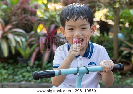 Close Up Young Asian Boy Eating A Lollipop