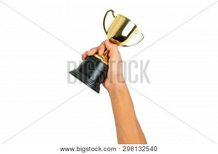 Boy holding up a gold trophy cup for kids isolated on white background for success and achievement concept. Gold trophy plastic for students.