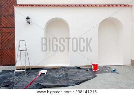Renovation, restoration, refurbishment. Painting accessories in front of empty exterior house wall poster