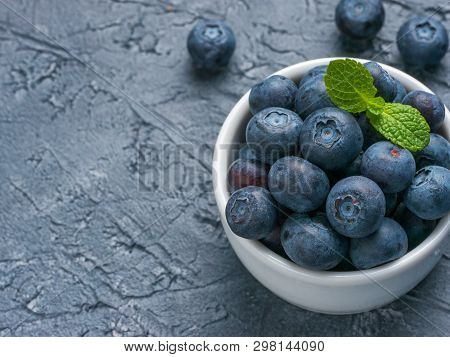 Freshly Picked Blueberries Closeup. Ripe And Juicy Fresh Blueberry With Green Mint Leaves On Texture