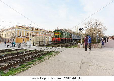 Feodosia, Crimea, Russia - March 08, 2019: A Passenger Train With A Green Electric Locomotive Arrive