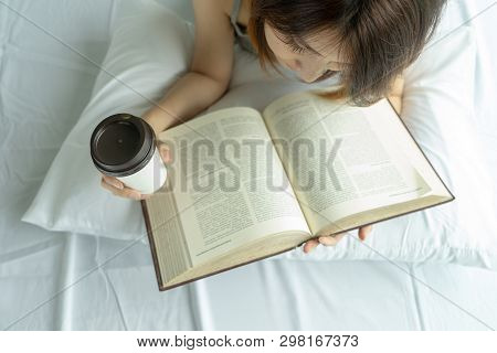 Young Woman Reading Book With Morning Coffee Cup In Bedroom At Home. Asian Girl Drink Tea Top View L
