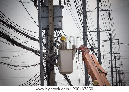Electricians Wiring Cable Repair Services. Technician Checking Fixing Broken Electric Wire On Pole.