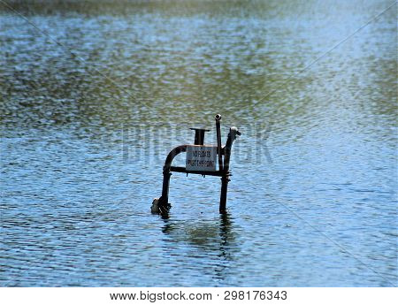 The Rusting Remains Of An Old Lifeguard Chair Rise Out Of The Calm, Cool Waters Of A Lake In Kentuck