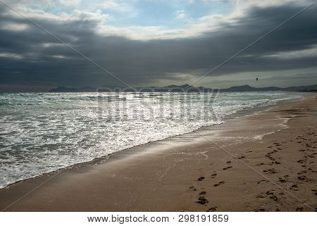 A Kitesurfer Surfs With A Red Kite On The Beach Of Mallorca