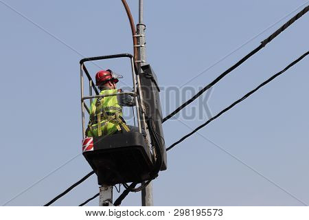Electrician Repairs The Street Light. Worker On The Lifting Platform Near The Lantern Against The Bl
