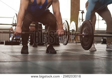 Close-up - Sporty Athletic Men Training With Barbells. Cross Fit Training. Handsome Men During Worko