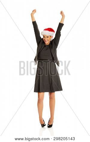 Full length of businesswoman with raised arms wearing christmas hat.