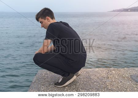 Young Man Crouching On A Pier, Looking Into The Sea