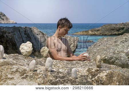 Young Man At The Sea Balances Stones On A Rock