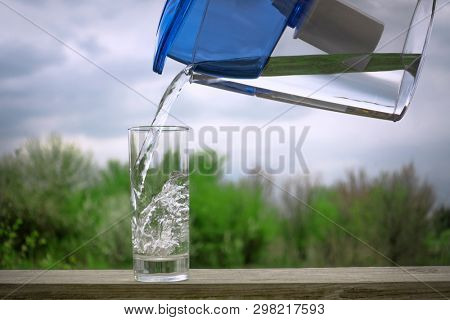 Cear filtered water pouring from a water filtration jug into a glass on the green summer garden background.