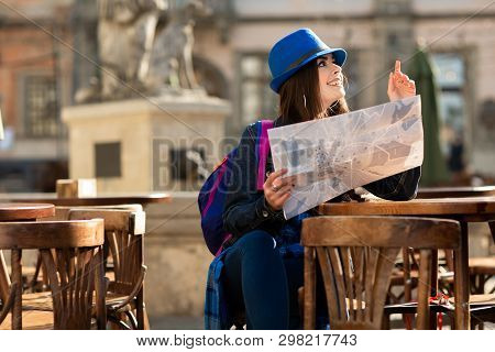 Young Girl In A Blue Hat Resting On The Summer Terrace In The Old Town, And Looking At The Map. Lviv