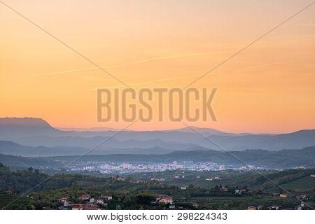 View Over Vineyards In Wine Region Brda On Sunrise To Town Nova Gorica With Julian Alps And Triglav