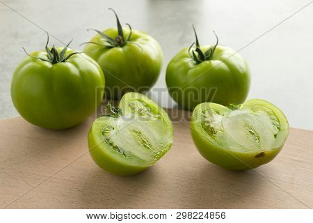 Whole and half fresh raw green unripe tomatoes on a cutteing board poster