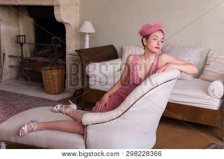 Sensual 1920s woman in pink flapper dress sitting on an antique chaisee longue or recliner