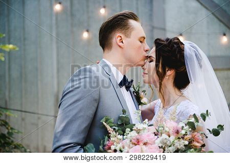Wedding. Portrait Of A Beautiful Bride And Groom. The Bride And Groom Walk In The Garden Against The