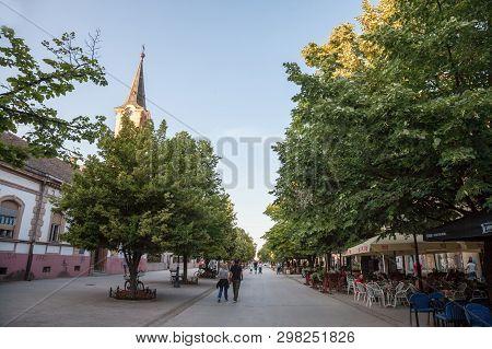 Indija, Serbia - May 20,  2018: Main Pedestrian Street Of Indjija, Ulica Vojvode Stepe, With A Chuch