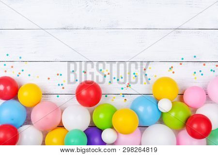 Colorful Balloons And Confetti On White Table Top View. Festive Or Party Background. Flat Lay. Birth