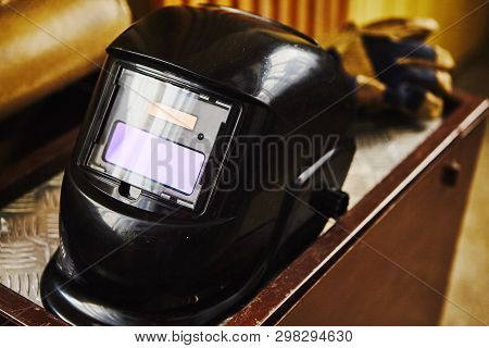 Welding equipments on table. Working tooling for industrial. Mask, gloves, electrodes. poster