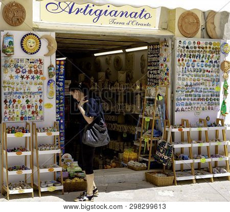 Otranto, Italy - May 19, 2018: Tourist Observes Souvenirs And Ceramic Objects In A Shop In The Histo