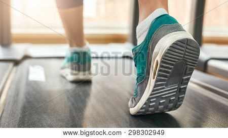 Cardio Workout. Cropped Photo Of Woman In Sports Shoes Running On Treadmill At Gym. Sport And Fitnes