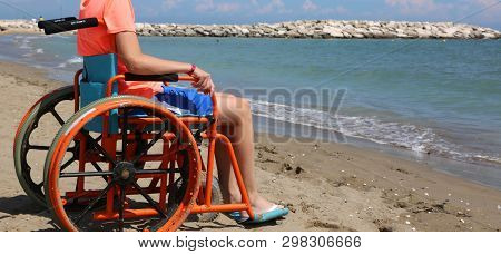 Boy With A Physical Disability Sits In A Wheelchair Facing The Sea