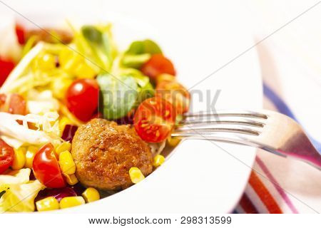 Colorful Fresh Vegetable Salad With Meatballs And Corn Seeds On Rustic Background