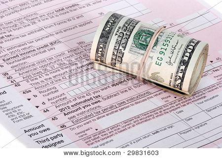 A Roll Of USD Cash Near An Irs Tax Form