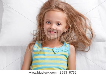 Photo Of Pleasant Looking Small Female Kid With Blue Eyes, Dressed In Nightwear, Has Satisfied Expre