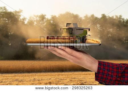 Farmer Holding A Tablet With A Combine Harvester. Augmented Reality And Digital Transformation In Ag