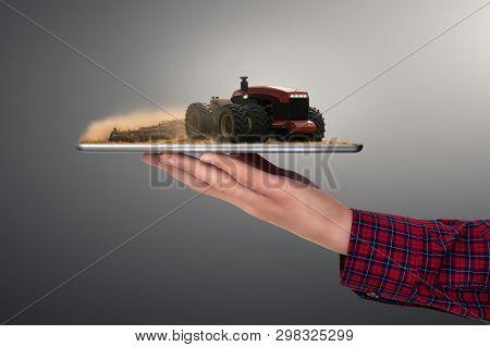Farmer Holding A Tablet With Autonomous Tractor. Smart Farming