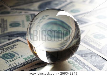 Glass Ball On Dollars. Dollar Banknotes And A Transparent Crystal Ball.