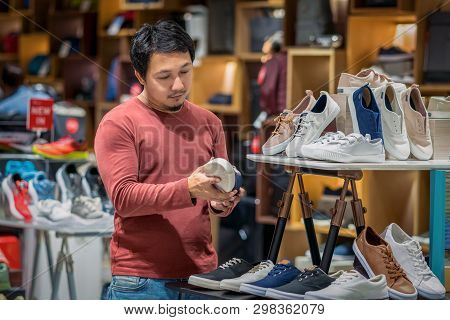 Smart Asian Man With Beard Choosing Fashion Shoes In Store Shop At Department Shopping Center, Beaut