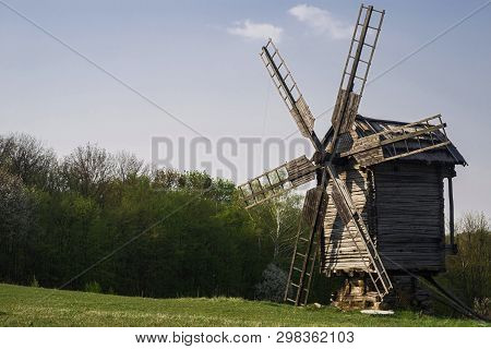 Wooden Windmill And Millstone On The Hillside Against A Background Of Forest And Blue Sky. Selective