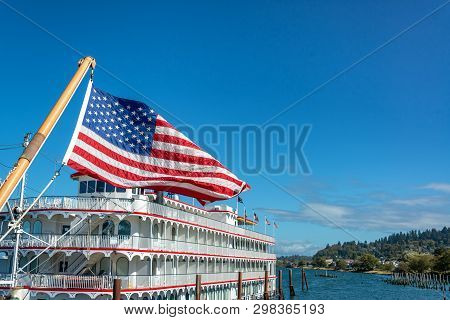 American Flag Waving In The Wind With An Old Time Riverboat In Beautiful Astoria, Oregon
