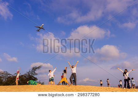 Phuket, Thailand - April 14, 2019: Tourists Enjoy Taking A Picture With The Airplane Flying Over The