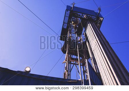 Oil And Gas Drilling Rig Onshore Dessert With Dramatic Cloudscape. Oil Drilling Rig Operation On The