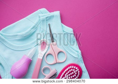 Newborn baby story. T-shirt and childrens toys, scissors, baby bottle, nipple, hairbrush on red background poster