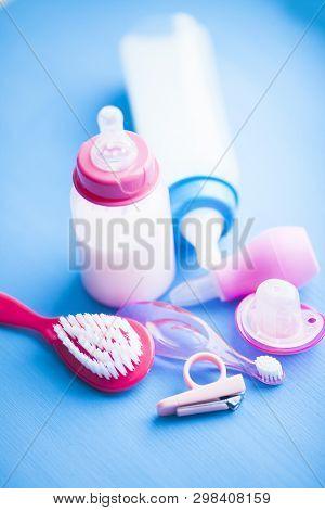 Newborn baby story. Childrens toys, scissors, baby bottle, nipple, hairbrush on blue background poster