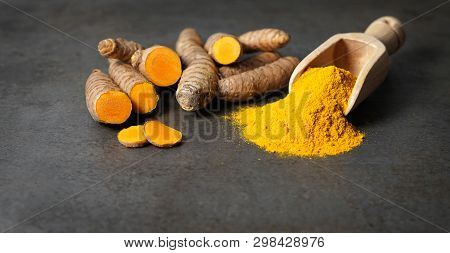 Turmeric Powder Healthy Spice Asian Food Closeup Of Turmeric Roots Sliced And A Wooden Bailer On A R