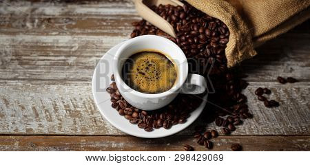 Coffee Cup And Roasted Coffee Beans In A Burlap Sack On A Wooden Rustic Table Top View On Rusty Vint