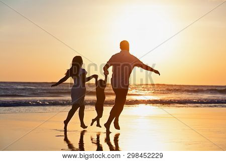 Happy Family Black Silhouette On Sun Background. Father, Mother, Baby Son Run. Child Jump With Fun B